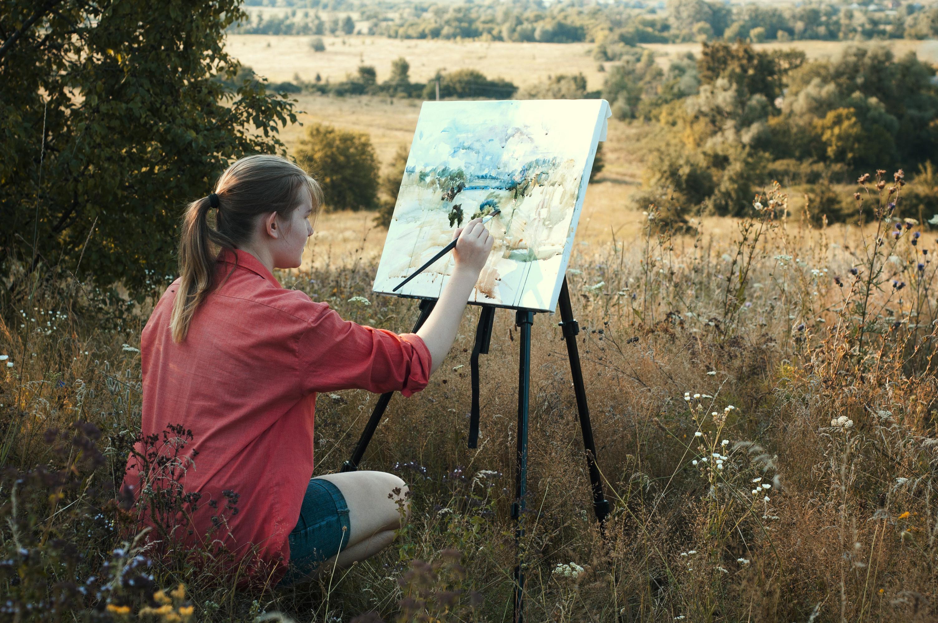 Das Foto zeigt eine junge Frau mit Staffelei in der Natur.