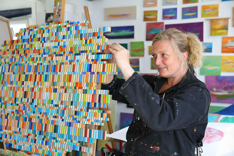 Abbildung der Künstlerin wie sie an einer Collage aus vielen farbigen Feldern arbeitet