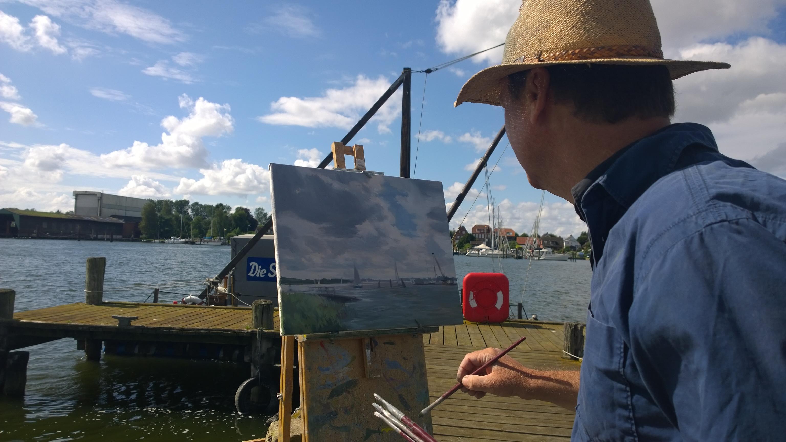 Abbildung des Künstlers vor seiner Leinwand auf einer Staffelei wie er am Ufer der Schlei die Landschaft malt